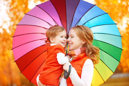 woman with umbrella: Happy family mum and child daughter with rainbow colored umbrella under rain on nature