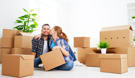 moving: moving to a new apartment. Happy family couple and a lot of cardboard boxes.