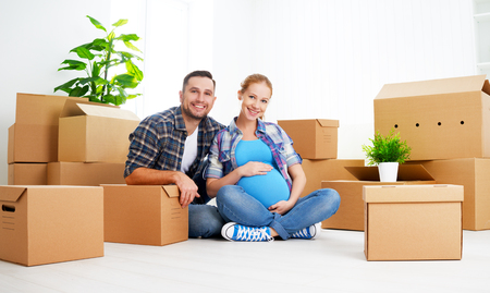 people moving: moving to a new apartment. young family pregnant wife and husband with cardboard boxes