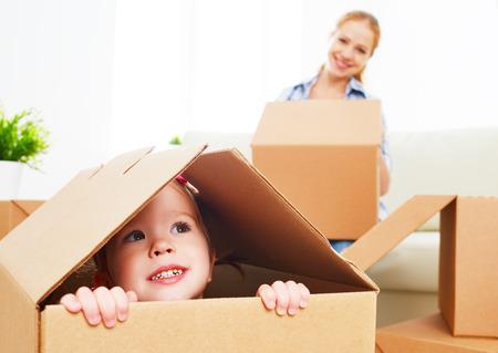 cajas de carton: familia feliz se muda a un nuevo apartamento. bebé feliz en una caja de cartón Foto de archivo