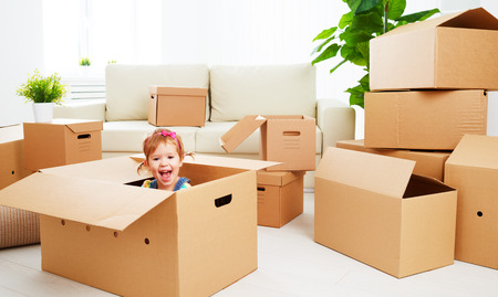 moving to a new apartment. happy child in a cardboard box Stok Fotoğraf