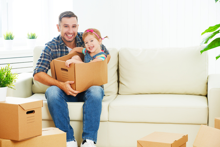 unpacking: happy family moves to new apartment. dad and child  daughter packs in cardboard boxes