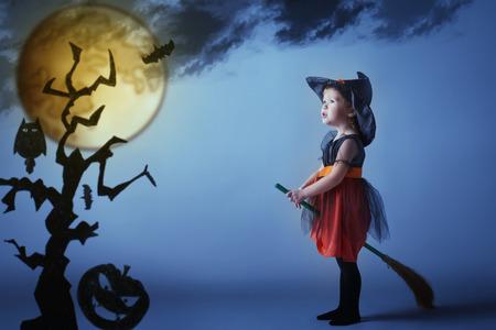 czarownica: Halloween. Czarownica dziecko latania na miotle na zachodzie słońca na nocnym niebie. Zdjęcie Seryjne