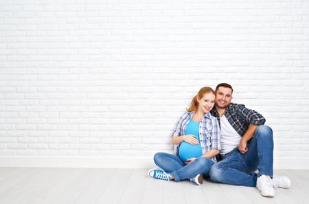 pareja en casa: feliz pareja de marido y mujer embarazada cerca de la pared de ladrillo en una habitación vacía