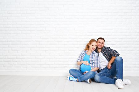 homme enceinte: heureux couple mari et femme enceinte près du mur de briques dans une salle vide