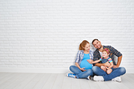 gia đình: cha hạnh phúc gia đình và người mẹ mang thai và con gái trẻ gần một bức tường gạch trống trong phòng