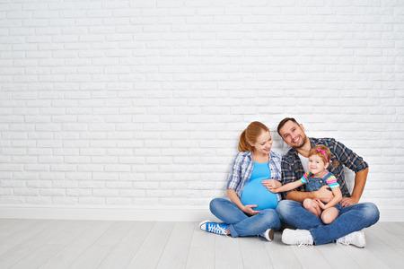families together: Padre feliz de la familia y la madre embarazada y su hija ni�o cerca de una pared de ladrillos en blanco en la habitaci�n
