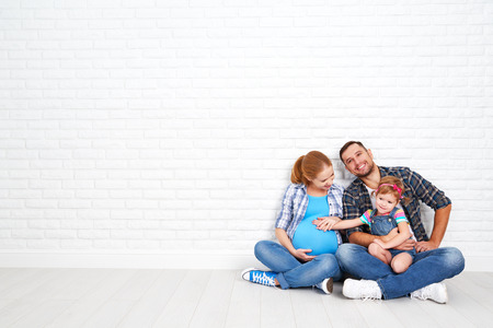 child couple: Happy family father and pregnant mother and child daughter near a blank brick wall in the room