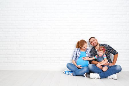 embarazadas estrenimiento: Padre feliz de la familia y la madre embarazada y su hija niño cerca de una pared de ladrillos en blanco en la habitación