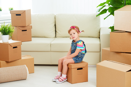 sala parto: moving to a new apartment. happy child and a cardboard box Archivio Fotografico