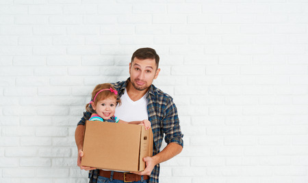 cardboard house: happy family moves to new apartment. dad and child  daughter playing  and have fun packs in cardboard boxes Stock Photo