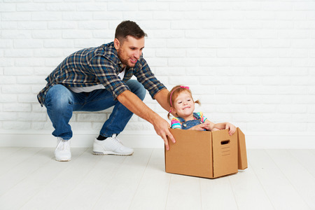 people moving: happy family moves to new apartment. dad and child  daughter playing  and have fun packs in cardboard boxes Stock Photo