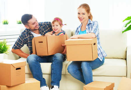 family moving house: moving to a new home. Happy family with cardboard boxes