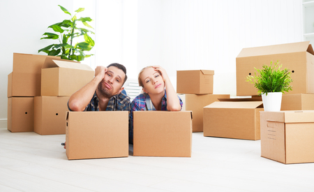 on the move: moving to a new apartment. tired family couple and a lot of cardboard boxes.