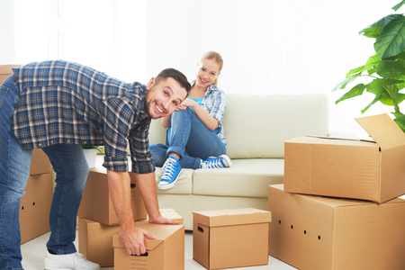 moving box: moving to a new apartment. Happy family couple and a lot of cardboard boxes.