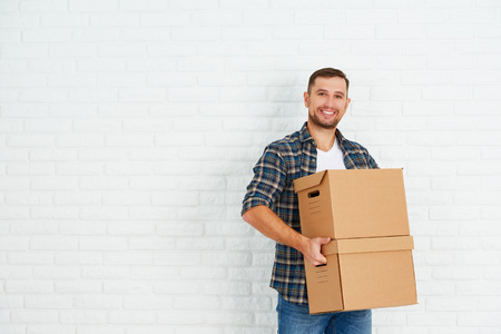 carrying: moving to a new apartment. Young happy man with cardboard boxes around the white brick wall