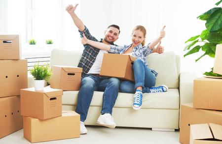 bienes raices: mudarse a un nuevo apartamento. Pareja feliz de la familia y un montón de cajas de cartón.