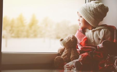 kinderen: kind meisje zitten bij het raam met een teddybeer en kijken naar de winter bos