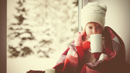 child little girl sitting by the window with a cup of hot tea and looking at the winter forest 免版税图像