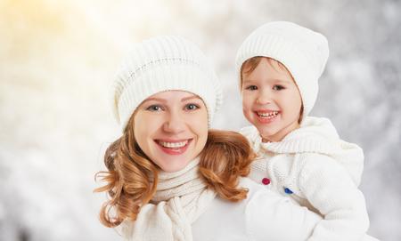 niños riendose: madre de familia feliz y su hija bebé niño en un paseo de invierno en el bosque Foto de archivo