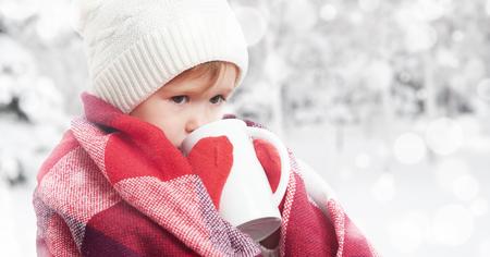 raffreddore: ragazza bambino felice con una tazza di bevanda calda in un freddo inverno all'aperto