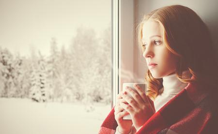 Nadenkend trieste meisje met een verwarmend drankje kijkt uit het raam in de winter bos