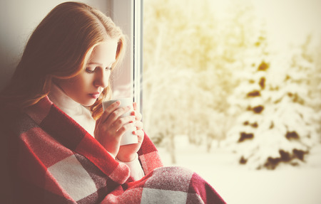 cold drinks: Pensive sad girl with a warming drink looking out the window in the winter forest Stock Photo