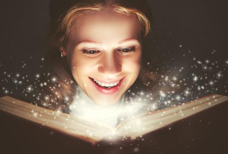 magia: mujer leyendo un libro mágico que brilla intensamente en la oscuridad