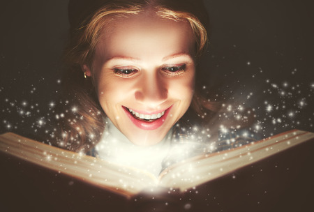 woman reading a magic book glowing in the dark Imagens