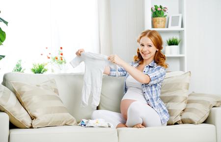 niños de compras: embarazada mujer embarazada mujer prepara artículos de ropa para el bebé recién nacido