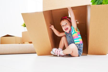 moving to a new apartment. happy child in a cardboard box Archivio Fotografico