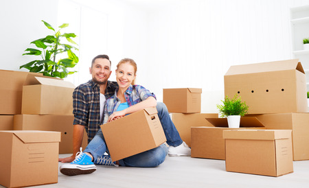 new home: moving to a new apartment. Happy family couple and a lot of cardboard boxes.