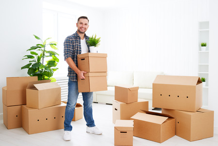 carrying box: moving to a new apartment. Young happy man with cardboard boxes