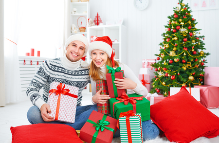 married: happy  family couple with a gift on Christmas morning at home Stock Photo