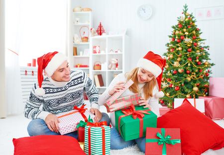christmas morning: happy  family couple with a gift on Christmas morning at home Stock Photo