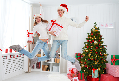 female portrait: Happy funny cheerful family couple jumping and having fun on Christmas at home