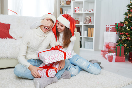 young tree: Christmas gift. woman gives a man a surprise gift present box Stock Photo