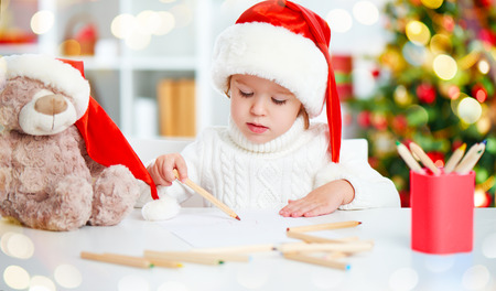 child girl before Christmas writes a letter to Santa Claus