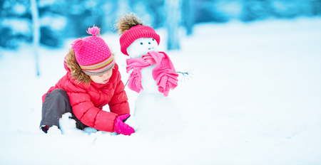 christmas fun: happy child girl with a snowman on a snowy winter walk Stock Photo