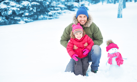 frosty the snowman: Happy family father and child girl makes a snowman walking outdoors in winter Stock Photo