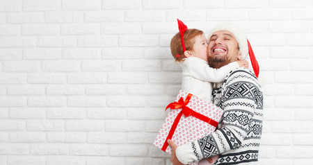 padres: Feliz padre de familia y el ni�o con un regalo en un beso de Navidad de una pared de ladrillos en blanco Foto de archivo