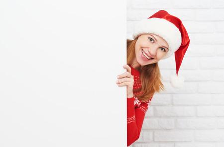 sombrero: mujer feliz en Navidad con un cartel en blanco vacío en blanco