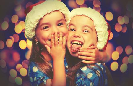 niñas gemelas: Feliz Navidad de los niños divertidos gemelos hermanas abrazan
