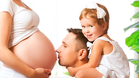 hands on stomach: Happy family. A father and child kisssing belly of mother pregnant
