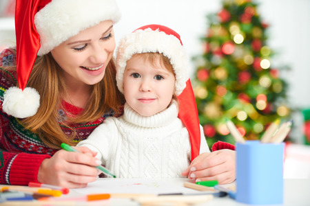 letter writing: happy family mother and baby child daughter  write a letter to Santa Claus on Christmas Eve