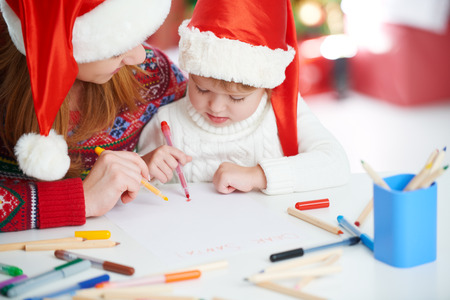 write a letter: happy family mother and baby child daughter  write a letter to Santa Claus on Christmas Eve