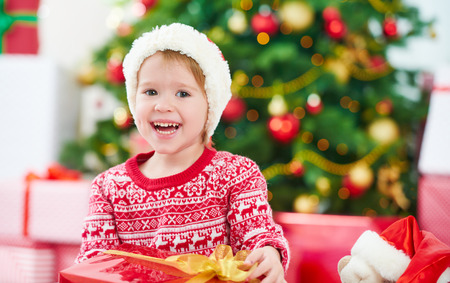 cute little girl smiling: happy child girl with Christmas gifts near a Christmas tree