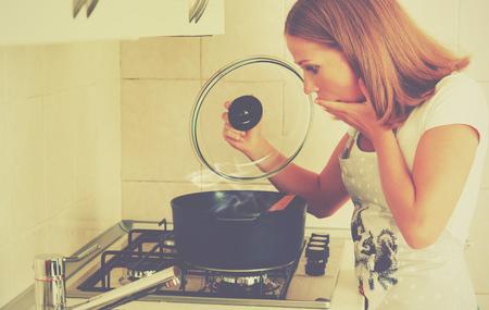 面白い女性主婦は、台所で準備します。焦げた食品