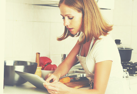 home cooking: woman housewife cooks food a recipe from the Internet with a tablet computer  in the kitchen