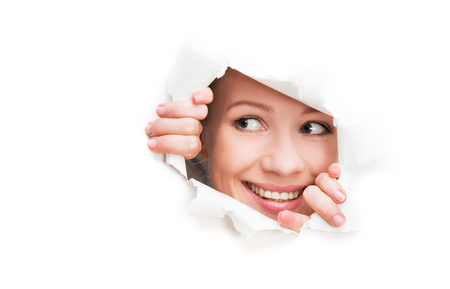 to break through: face of a young curious woman peeking through a  hole torn in white paper poster